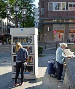 Öffentlicher Bücherschrank in Essen, NRW (am Grillo-Theater) mit interessierten Leserinnen. Foto: Wikipedia. CC BY-SA 3.0