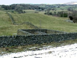 "Landschaft: Andy Goldsworthy: sheepfolds near Crook in the Lake District in the winter of 2006. ""fold1"". The fist sheep fold with tree growing through a boulder. Foto: Dave Bleasdale. Creative Commons Attribution-Share Alike 3.0 Europe"