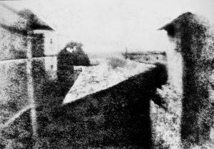 """Blick aus dem Arbeitszimmer von Le Gras (französischer Titel La cour du domaine du Gras """"Der Hof des Gutshofes von Le Gras"""" oder Point de vue du Gras """"Ansicht von Le Gras"""") ist die erste erfolgreich aufgenommene und erhaltene Fotografie der Welt. Sie wurde von Joseph Nicéphore Nièpce im französischen Saint-Loup-de-Varennes hergestellt. Das Foto zeigt den Blick aus dem Arbeitszimmer von Nièpces Gutshof Le Gras. Von der linken Seite her sieht ein Betrachter zunächst den Rahmen des Fensterflügels, das turmartige Taubenhaus des Gutshofs, weiter entfernt einen Baum, ein kleines Gebäude mit Pultdach und schließlich einen turmförmigen Kamin, wahrscheinlich vom Backhaus. Quelle: Rebecca A. Moss, Coordinator of Visual Resources and Digital Content Library, via email. College of Liberal Arts Office of Information Technology, University of Minnesota. http://www.dcl.umn.edu"""