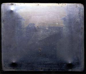 Joseph Nicéphore Niépce (Foto um 1826): Blick aus dem Arbeitszimmer in Le Gras. 20×25 cm auf ölbehandeltem Asphalt. Durch die 8-stündige Belichtungszeit erscheinen die Gebäude sowohl rechter- als auch linkerhand sonnenbeschienen. Dieses Foto gilt allgemein als erstes der Welt. Originalfotoplatte, um 1826. Quelle: Harry Ransom Center's Gernsheim collection, The University of Texas at Austin. Gemeinfrei