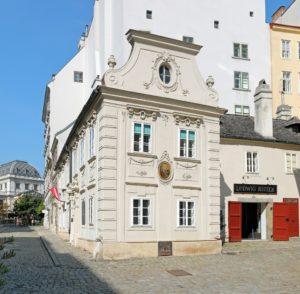 Das sogenannte Dreimäderlhaus an der Adresse Schreyvogelgasse 10 im 1. Wiener Gemeindebezirk Innere Stadt. Links im Hintergrund das Hauptgebäude der Wiener Universität. © Bwag/CC-BY-SA-4.0.
