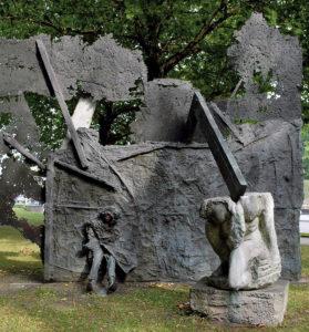"""Alfred Hrdlicka hat den """"Hamburger Feuersturm"""", """"Cap Arcona"""", """"Soldatentod"""" und """"Frauenbild im Faschismus"""" in seinem Kunstwerk thematisiert. Der erste Teil, der Feuersturm, erinnert an die Feuerwalzen, die durch Hamburgs Straßen während der Operation Gomorrha zogen. Der erste Teil des Gegendenkmals wurde am 8. Mai 1985 eingeweiht. Der zweite Teil wurde Ende September 1986 der Öffentlichkeit übergeben. Dieses Kunstwerk taucht in der Namensgebung mal als """"Cap Arcona"""", mal """"Untergang von KZ-Häftlingen"""", aber auch """"Verfolgung und Widerstand"""". Gemeint ist das Schiff Cap Arcona, die am 3. Mai 1945 vor Lübeck durch Luftangriffe der Royal Air Force versenkt wurde. Die beiden letzten Themen des Gegendenkmals wurden vom Künstler nicht ausgeführt. Foto: © Kulturbehörde Hamburg. Foto: © Helge Mundt"""