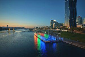"""Flüsse als Kulturort: """"Danube Jumping"""" (Trampolinkonzert) mit Blick auf DC-Tower, Kaisermühlen und Bruckhaufen in Wien. Foto: Johannes Hloch"""