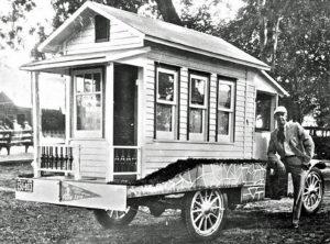 """Pressefoto: Der Fotograf Charles Miller neben seinem mobilen Tiny House. """"Der 'Ogden Standard Examiner' vom 25. Juli 1929 gab an, dass das mobile Haus ein weiß-grüner Bungalow sei und auf dem Weg von Portland, Oregon, nach Salt Lake City, Utah, reise. Von dort wolle Charles Miller weiter nach Nevada fahren. Insgesamt soll Miller 200.000 Meilen mit seinem Haus gefahren sein. Zu den Annehmlichkeiten des Tiny House gehörten ein Bett, ein Radio und Kochutensilien – allerdings fehlte ein Herd – den er später einbauen lassen wollte."""" Pressefoto, Autor unbekannt. Quelle: http://theoldmotor.com"""